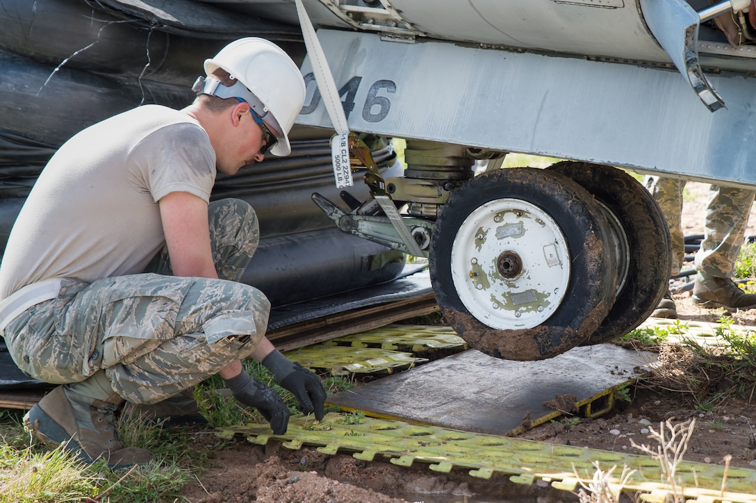 U.S. Air Force Staff Sgt. Ronald Bahre with the 153rd Maintenance Group's Crash Damage or Disabled Aircraft Recovery team places steel planking beneath the front landing gear of an A-7 Corsair II aircraft, May 11, 2017 in Cheyenne, Wyoming. Maintainers from all aircraft specialties practiced moving a fighter aircraft from the mud into a parking spot as part of an annual CDDAR requirement. (U.S. Air National Guard photo by Senior Master Sgt. Charles Delano/released)