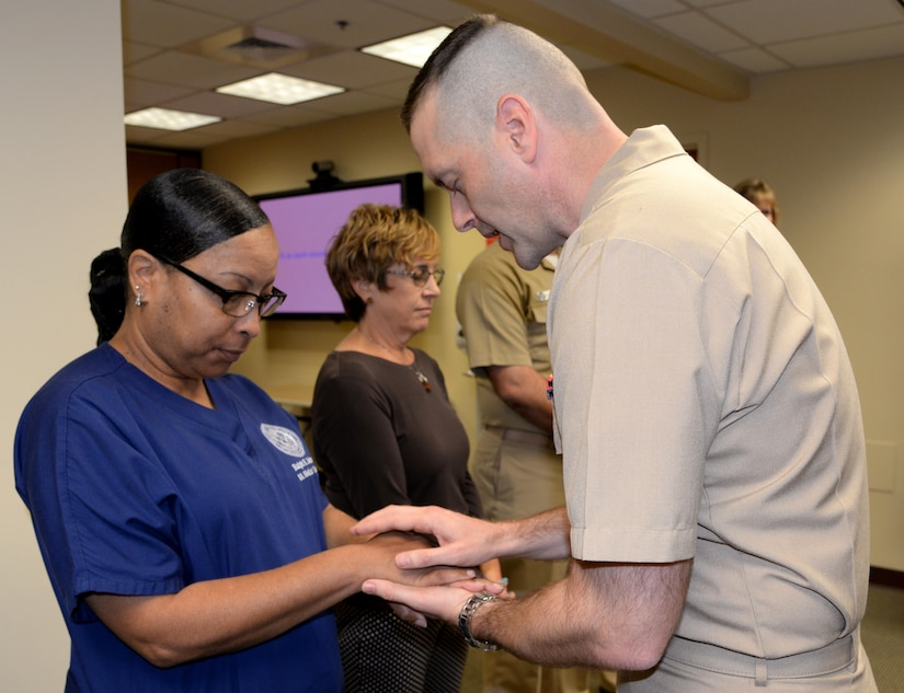 """Lt. Grant Mayfield, right, chaplain, Naval Support Activity, blesses the hands of Stacey Belton, nurse, Veterans Affairs Goose Creek Outpatient Clinic, during a """"Blessing of the Hands"""" ceremony May 8 at Naval Health Clinic Charleston located on Joint Base Charleston - Weapons Station, in celebration of Nurses Week May 6-12. The """"Blessing of the Hands"""" ceremony, a hospital tradition practiced around the world during Nurses Week, honors nurses who use their hands in many ways to bring healing to patients."""