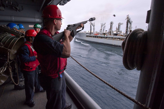 Gunner's Mate 3rd Class Ryan Sawhook, from Fairfield, Ohio, assigned to the weapons department aboard the amphibious assault ship USS America (LHA 6), fires a shot line with an M14 rifle to the fleet replenishment oiler USNS Henry J. Kaiser (T-AO 187) during a replenishment-at-sea, May 11, 2017. More than 1,800 Sailors and 2,600 Marines assigned to the America Amphibious Ready Group (ARG) and the 15th Marine Expeditionary Unit (15th MEU) are conducting a composite training unit exercise (COMPTUEX) off the coast of Southern California in preparation for the ARG's deployment later this year. The America ARG is comprised of America, the amphibious dock landing ship USS Pearl Harbor (LSD 52), and the amphibious transport dock ship USS San Diego (LPD 22).