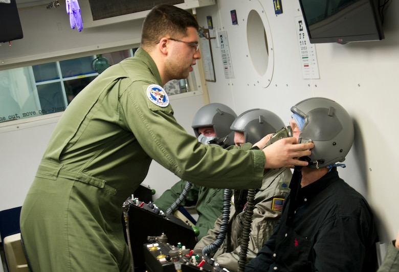 Senior Airman Christopher Connolly, 779th Aerospace Medical Squadron physiologist, assists David Kinsella with sealing his oxygen mask inside an altitude simulator chamber March 16, 2017, at Joint Base Andrews, Md. As an inside observer, Connolly was nearby to assist if Kinsella or the other students had physiological complications while experiencing varying levels of air pressure. (U.S. Air Force photo by Staff Sgt. Joe Yanik)