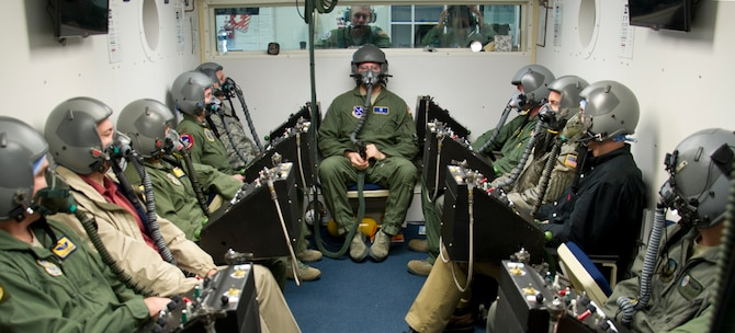 Senior Airman Christopher Connolly (center sitting), 779th Aerospace Medical Squadron physiologist, and students await the beginning of their altitude training course while inside an enclosed chamber March 16, 2017, at Joint Base Andrews, Md. All of the students were undergoing refresher training, required every five years, to test their ability to identify how their bodies reacted in an environment with varying levels of air pressure. (U.S. Air Force photo by Staff Sgt. Joe Yanik)
