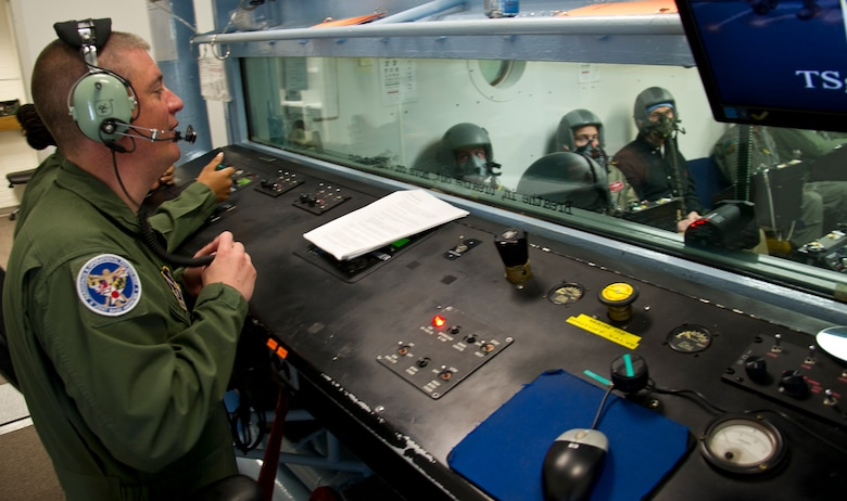 Tech. Sgt. Nicholas Haight (left), 779th Aerospace Medical Squadron flight chief, explains hypoxia symptoms to military and civilian personnel sitting inside an altitude chamber during flight simulation training March 16, 2017, at Joint Base Andrews, Md. Later in the training, the students were exposed to varying levels of air pressure as they would experience at different altitudes. (U.S. Air Force photo by Staff Sgt. Joe Yanik)