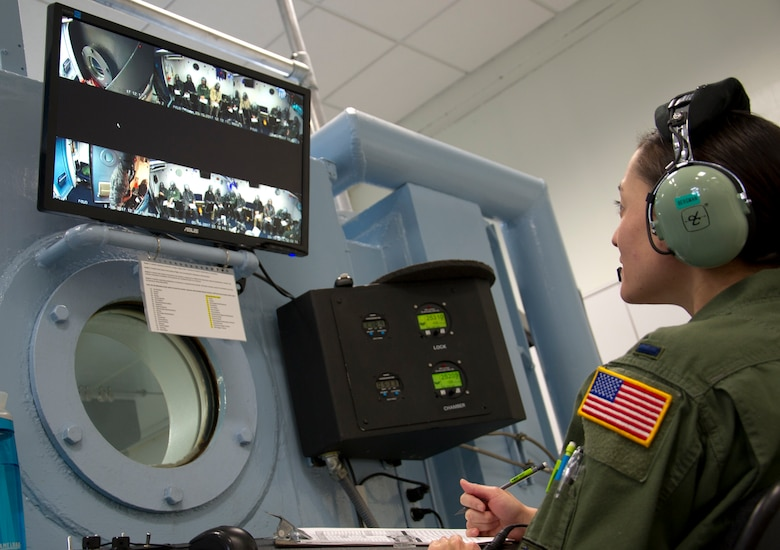 1st Lt. Alethea Bergman, 779th Aerospace Medical Squadron operations chief, monitors the altitude chamber's communications systems and the behavior of the students as they train in an enclosed altitude chamber March 16, 2017 at Joint Base Andrews, Md. From outside the chamber, she also kept watch on the amount of time the students were exposed to varying levels of air pressure without wearing their oxygen masks.  (U.S. Air Force photo by Staff Sgt. Joe Yanik)