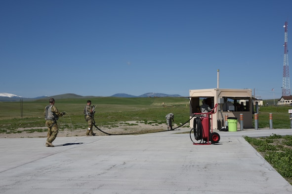 Aircrew from the 40th Helicopter Squadron work with Tech. Sgt. Nathan Wiley, 10th Missile Squadron facility manager, to return a hose back to a missile field refueler after refueling May 11, 2017, at Malmstrom Air Force Base, Mont. This was the seventh completed missile alert facility helicopter refuel completed at Malmstrom. (U.S. Air Force photo/ Staff Sgt. Delia Marchick)