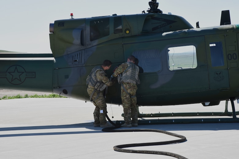 Aircrew from the 40th Helicopter Squadron refuel a UH-1N helicopter at a missile alert facility May 11, 2017, at Malmstrom Air Force Base, Mont. The 40th HS coordinates with the facility manager at MAFs equipped with refueling stations for rapid refuels during missions in the missile field. (U.S. Air Force photo/ Staff Sgt. Delia Marchick)