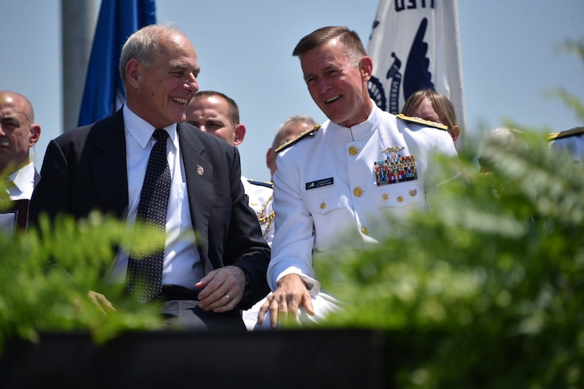 Secretary of Homeland Security John F. Kelly and Coast Guard Commandant Adm. Paul F. Zukunft share a light moment during the 136th U.S. Coast Guard Academy Commencement in New London, Conn., May 17, 2017. Both leaders addressed the graduating class at the ceremony. Coast Guard photo by Petty Officer 2nd Class Patrick Kelley