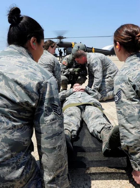 Airmen from the 8th Medical Group prepare to carry a simulated patient to a UH-60 Black Hawk medevac helicopter at Kunsan Air Base, Republic of Korea, May 17, 2017. The purpose of the training was aimed to train medics on loading patients onto a helicopter for dust-off. (U.S. Air Force photo/Staff Sgt. Chelsea Sweatt)