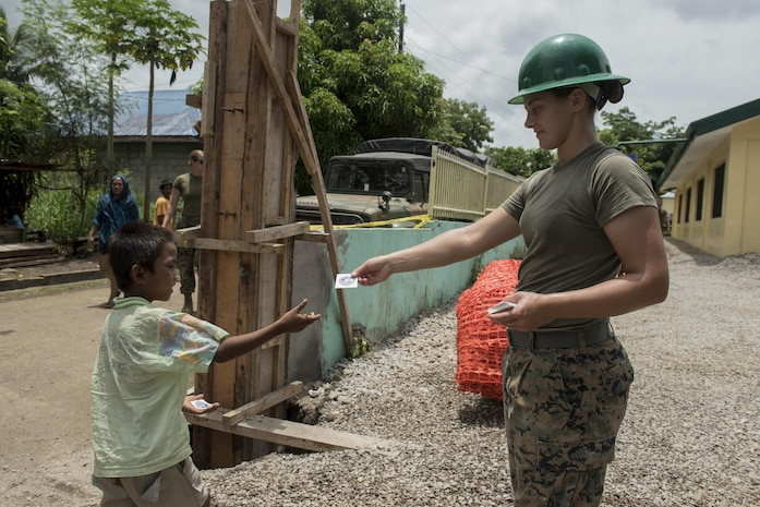 U.S. Marine Lance Cpl. Brook Klahn, right, gives a Balikatan sticker to a boy at an engineering civic assistance project site in support of Balikatan 2017 in Ormoc City, Leyte, May 14, 2017. Philippine and U.S. service members worked together to build new classrooms for students at Don Carlos Elementary School. Balikatan is an annual U.S.-Philippine bilateral military exercise focused on a variety of missions, including humanitarian assistance and disaster relief, counterterrorism, and other combined military operations.