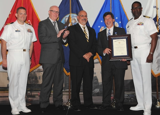 """DAHLGREN, Va. (May 17, 2017) - Stephen Malyevac holds a framed certificate moments after receiving the Navy Superior Civilian Service Award at the Naval Surface Warfare Center Dahlgren Division (NSWCDD) Annual Honor Awards ceremony. Malyevac was recognized for numerous technical and leadership contributions as the NSWCDD Distinguished Engineer for Surface Engagement. """"His accomplishments as a nationally recognized expert in guidance and control, missile systems, guided projectiles, and surface weapon systems have played a critical role in establishing Dahlgren Division's reputation as a center of excellence for weapon system engineering and integration,"""" according to the citation. """"Mr. Malyevac's leadership on numerous high profile technical efforts has resulted in the successful fielding of many of the technologies and capabilities that form the foundation of our surface fleet today.""""  Standing left to right: Combat Direction Systems Activity Commanding Officer Cmdr. Andrew Hoffman; Naval Surface Warfare Center and Naval Undersea Warfare Center Executive Director Donald McCormack; NSWCDD Technical Director John Fiore; Malyevac; and NSWCDD Commanding Officer Capt. Godfrey 'Gus' Weekes."""