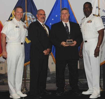 """DAHLGREN, Va. (May 17, 2017) - Joseph Berenotto holds  the John Adolphus Dahlgren Award moments after receiving it from Naval Surface Warfare Center Dahlgren Division (NSWCDD) leadership at the command's annual honor awards ceremony. Berenotto was recognized for his outstanding contributions to the Submarine Launched Ballistic Missile program and NSWCDD. """"Mr. Berenotto's visionary thinking and demonstrated technical leadership in employment engineering, system simulation, modeling and analysis have greatly benefited Navy strategic systems and NSWCDD's role in this program's unparalleled record of readiness and reliability,"""" according to the citation. Standing left to right: Combat Direction Systems Activity Commanding Officer Cmdr. Andrew Hoffman; NSWCDD Technical Director John Fiore; Berenotto; and NSWCDD Commanding Officer Capt. Godfrey 'Gus' Weekes."""