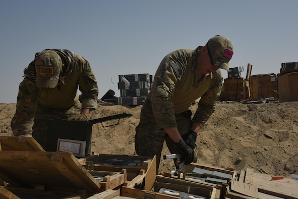 Two explosive ordnance disposal technicians, with the 386th Expeditionary Civil Engineer Squadron, place flares inside wooden crates during an ammunition disposal request burn operation at an undisclosed location in Southwest Asia May 11, 2017. The stockpile of expired munitions consisting primarily of flares was transported to an isolated location where the unserviceable items were stacked in a man-made hole in preparation for destruction. (U.S. Air Force photo/Tech. Sgt. Jonathan Hehnly)