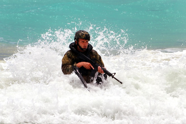 Army Pfc. Devin Doty moves through the water onto the beach at Marine Corps Training Area Bellows, Hawaii, May 16, 2017, during helocast insertion training. Doty is an infantryman assigned to the 25th Infantry Division's 3rd Squadron, 4th Cavalry Regiment, 3rd Brigade Combat Team. Army photo by Staff Sgt. Armando R. Limon