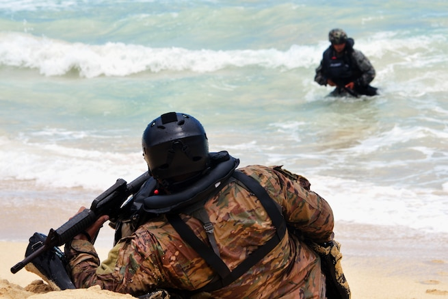 Team members move ashore at Marine Corps Training Area Bellows, Hawaii, May 16, 2017, during helocast insertion training. Army photo by Staff Sgt. Armando R. Limon