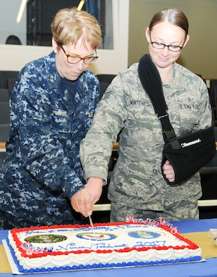 Rear Adm. Rebecca McCormick-Boyle (left), commander, Navy Medicine Education, Training and Logistics Command, cuts a ceremonial cake with Staff Sgt. Kaitlyn Montenegro during a celebration for National Nurses Week at the Medical Education and Training Campus at Joint Base San Antonio-Fort Sam Houston May 11. Navy and Air Force nurses and medical technicians participated together in several health promotions activities throughout the week to commemorate Nurses Week.