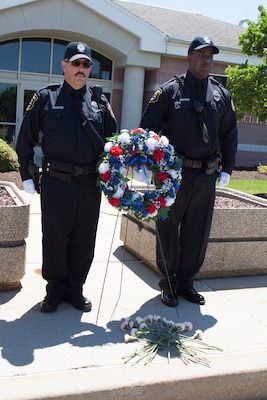 DLA police officers James Powers, Jr. (left) and Durran Topp, Jr. (right) stand guard of the memorial wreath and carnations during the DLA Distribution National Police Week wreath laying ceremony held on May 15.