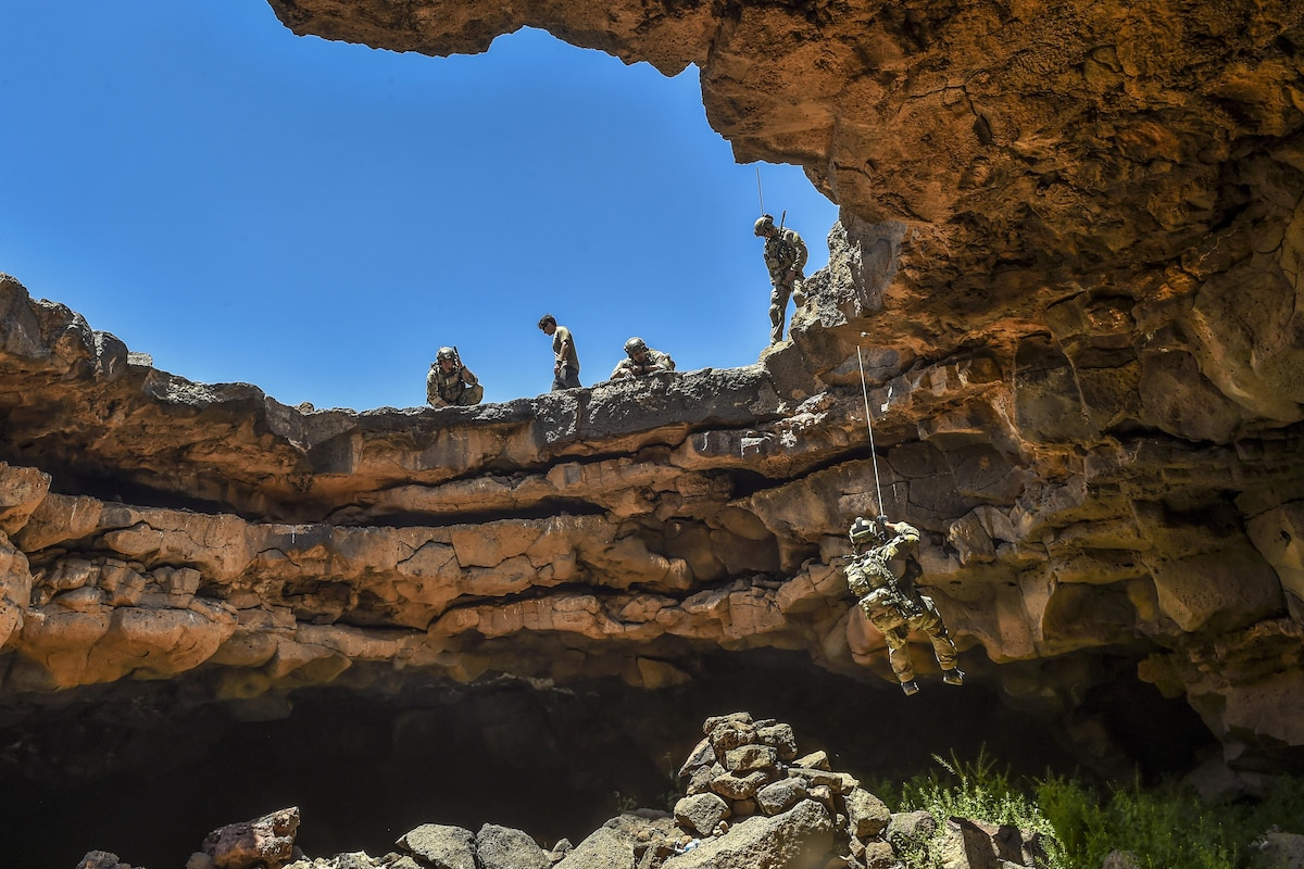 An airman rappels into a cave complex with blue skies overhead.