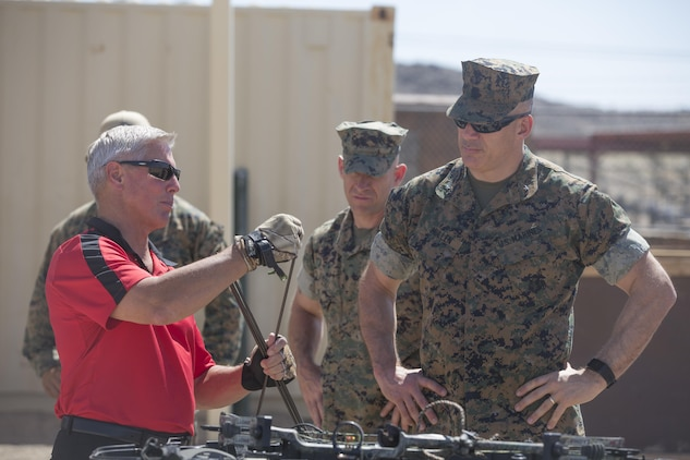 Combat Center leadership learn about the different parts of a bow and arrow from Creg McDonald, liaison to Marine Air Ground Task Force Training Command, Joint Improvised Threat Defeat Organization, during the opening of the Combat Center's new archery range on Range 3A aboard Marine Corps Air Ground Combat Center, Twentynine Palms, Calif., May 11, 2017. The idea was proposed through the installation's newly-implemented Facebook group, Make the Stumps Better, which is an initiative proliferated by Combat Center Commanding General, Brig. Gen. William F. Mullen III, in order to solicit opinions and concerns from Combat Center patrons and determine actionable change from leadership.(U.S. Marine Corps photo by Cpl. Thomas Mudd)