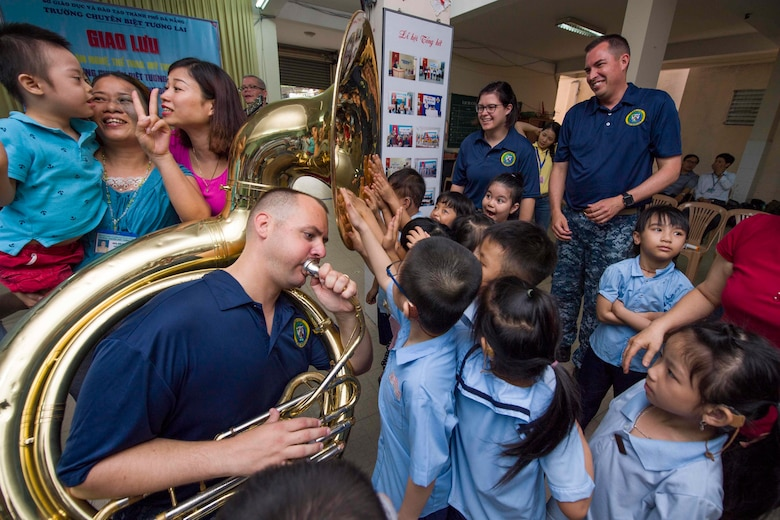 Musician 2nd Class James Brownell of the U.S. 7th Fleet Band plays the tuba for hearing impaired students to feel the sound vibrations with their hands during a community engagement at Tuong Lai Specialized School, May 10, 2017. Pacific Partnership is the largest annual multilateral humanitarian assistance and disaster relief preparedness mission conducted in the Indo-Asia-Pacific and aims to enhance regional coordination in such as medical readiness and preparedness for manmade and natural disasters.