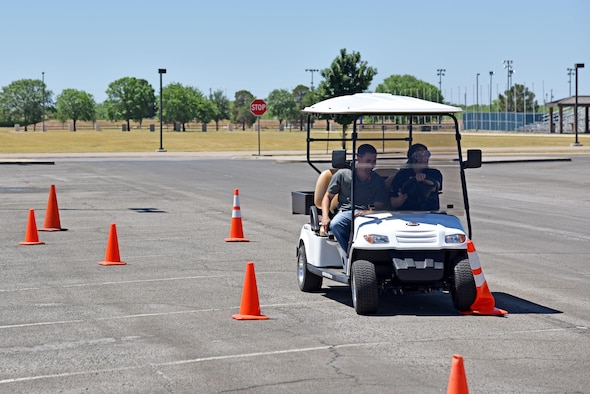 Tiffanie De La Cruz, Goodfellow Exchange junior manager, drives a golf cart during a simulated drunk driving course for Police Week at the commissary on Goodfellow Air Force Base, Texas, May 17, 2017. The 17th Security Forces Squadron held the course to raise awareness on drunk driving and the dangers it can cause. (U.S. Air Force photo by Staff Sgt. Joshua Edwards/Released)