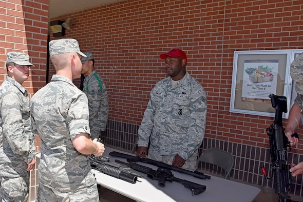 Senior Airman Devin Jemison, 17th Security Forces Squadron combat arms instructor, tells Airmen about different Air Force weaponry at the commissary on Goodfellow Air Force Base, Texas, May 17, 2017. As part of Police Week, the 17th SFS gave back to the base by providing displays and demonstrations. (U.S. Air Force photo by Staff Sgt. Joshua Edwards/Released)