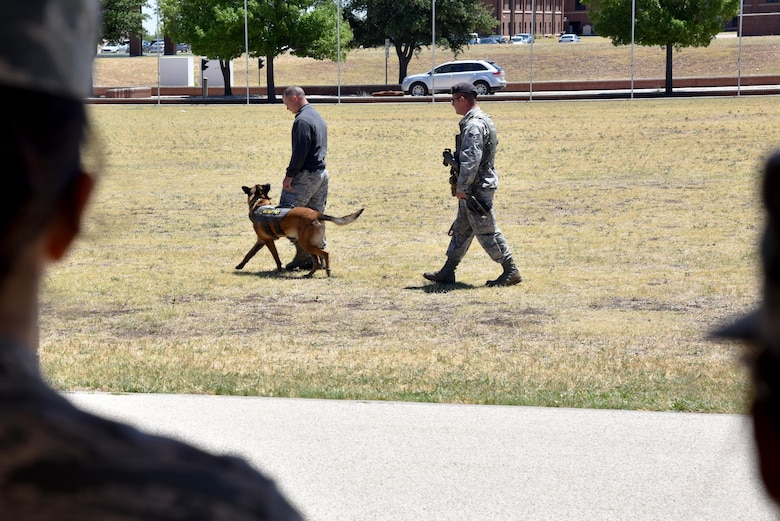 Spike, 17th Security Forces Squadron military working dog, guards his prisoner Staff Sgt. Dakota Riddle, 17th SFS MWD handler, at the parade grounds on Goodfellow Air Force Base, Texas, May 17, 2017. The 17th SFS provided fingerprinting, a weapons display and K-9 demonstration as part of Police Week. (U.S. Air Force photo by Staff Sgt. Joshua Edwards/Released)