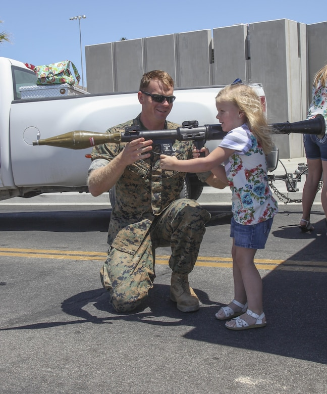 Staff Sgt. Robert Bouchard, technician, Explosive Ordinance Disposal, helps his daughter Tenley, 3, hold an unarmed RPG during the annual We Salute You Fest at Victory Field aboard the Marine Corps Air Ground Combat Center, Twentynine Palms, Calif., Saturday. Marine Corps Community Services hosts the event to show their appreciation for all the hard working service members who protect this country.