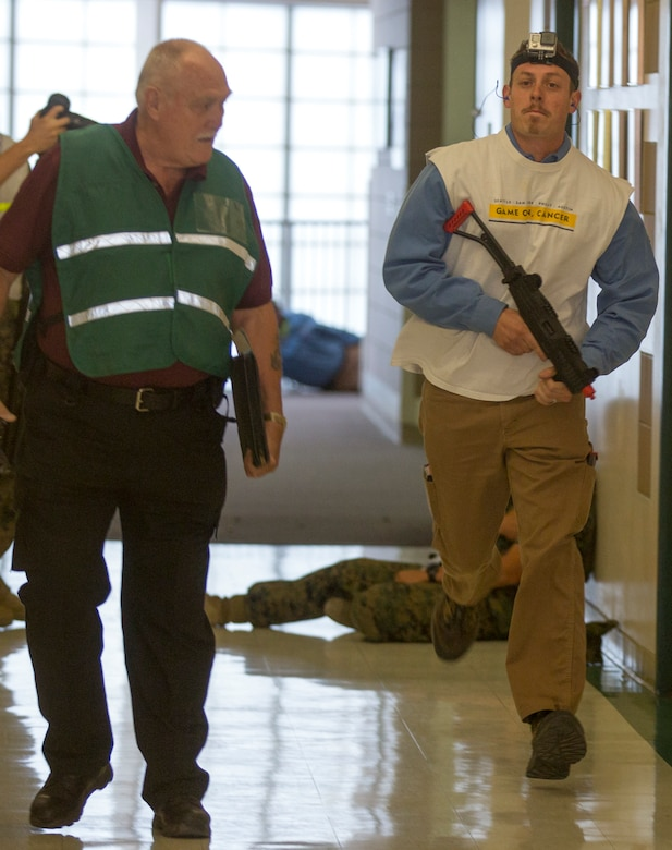 A simulated active shooter runs down a hall way during an Active Shooter Full Scale Exercise at Robert E. Bush Naval Hospital, aboard Marine Corps Air Ground Combat Center Twetynine Palms, Calif., May 16, 2017. The exercise allowed for the naval hospital, Provost Marshals Office, Fire Department and Naval Criminal Investigative Service to practice and assess their ability to detect, identify and respond to an active shooter incident, validating emergency response procedures. (U.S.Marine Corps photo by Cpl. Thomas Mudd)