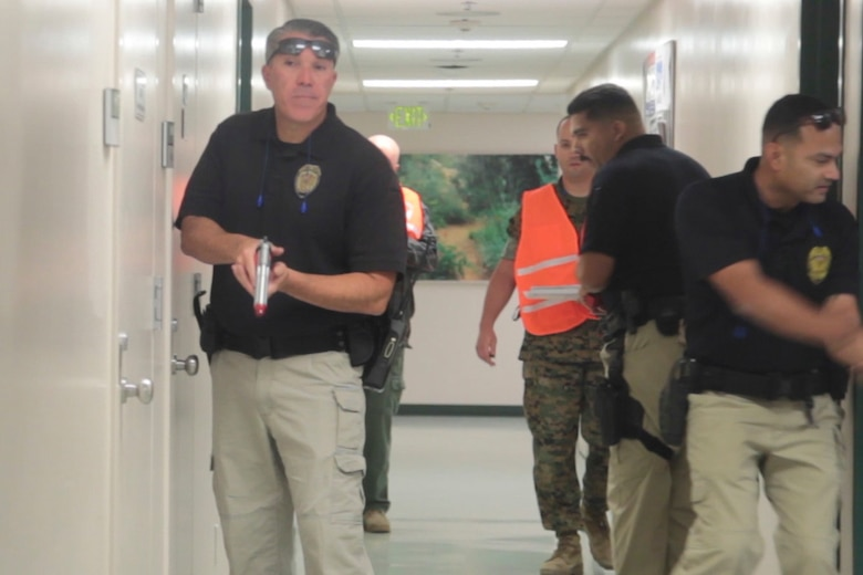 Officers from the Provost Marshal's Office check rooms of Robert E. Bush Naval Hospital during an Active Shooter Full Scale Exercise aboard Marine Corps Air Ground Combat Center Twetynine Palms, Calif., May 16, 2017. The exercise allowed for the naval hospital, Provost Marshals Office, Fire Department and Naval Criminal Investigative Service to practice and assess their ability to detect, identify and respond to an active shooter incident, validating emergency response procedures. (U.S. Marine Corps photo by Cpl. Thomas Mudd)