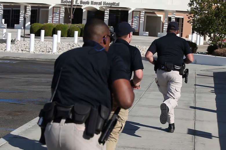 Officers from the Provost Marshal's Office respond to gun fire in the Naval Hospital Twentynine Palms during an Active Shooter Exercise, May 16, 2017. The exercise allowed for the naval hospital, Provost Marshals Office, Fire Department and Naval Criminal Investigative Service to practice and assess their ability to detect, identify and respond to an active shooter incident, validating emergency response procedures. (U.S. Marine Corps photo by Cpl. Thomas Mudd)