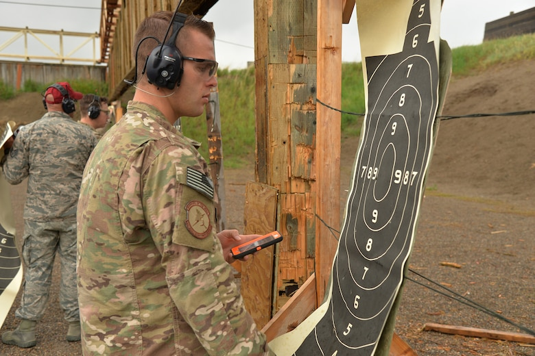 Staff Sgt. Alex Callahan, 741st Missile Security Forces Squadron tactical response force NCO in charge of the armory, counts points on a target at a shooting competition during National Police Week May 17, 2017, at Malmstrom Air Force Base, Mont. Participants in the shooting competition took turns performing different timed drills while accumulating points toward an overall score. (U.S. Air Force photo/Airman 1st Class Daniel Brosam)