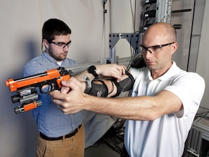 Researchers use high-speed motion sensor OptiTrack cameras mounted around the test area to monitor the mechatronic arm exoskeleton's effect on simulated shooting.