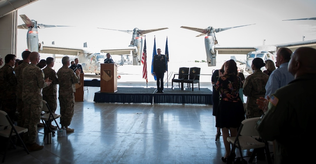 Maj. William Mendel, 20th Special Operations Squadron, stands at attention in front of a crowd attending his Distinguished Flying Cross ceremony at Cannon Air Force Base, N.M., May 15, 2017. Mendel's aircraft, along with other aircraft in his formation, received heavy and effective hostile fire during a mission in Africa. Despite the significant damage to the aircraft, Mendel managed to complete the mission and save the lives of four critically wounded individuals onboard. He and other crew members were presented the Distinguished Flying Cross, a medal created in 1918 to reward those who display heroism or extraordinary achievement while participating in an aerial flight. Mendel became the 79th Airman under Air Force Special Operations Command to receive the honor. (U.S. Air Force photo by Senior Airman Lane T. Plummer)