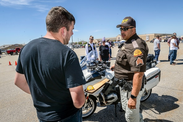 Sgt. Donavan Lucas of the Utah Highway Patrol talks motorcycle safety with a Hill Air Force Base employee, May 11. Besides safety briefings and demonstrations, Hill AFB's 3rd Annual Motorcycle Rodeo featured food, vendor displays and radio programming. (U.S. Air Force/Paul Holcomb)