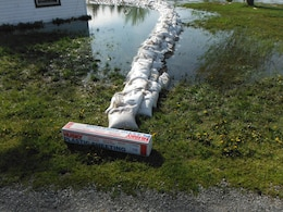 A U.S. Army Corps of Engineers Buffalo District Technical Assistance Field Team provided guidance on sandbag protection around a private residence in Lyme, New York. Plastic sheeting was deployed over the sand bag placement to mitigate water seepage.