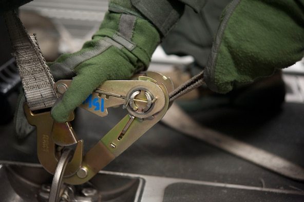 A U.S. Airman assigned to the 18th Aerospace Evacuation Squadron (AES) tightens down a latch to secure equipment May 13, 2017, at Kadena Air Base, Japan. The 18th AES deploys, establishes and operates elements of a theater aeromedical evacuation system, including a mobile staging facility, evacuation command and control and crew for worldwide taskings. (U.S. Air Force photo by Senior Airman Quay Drawdy)