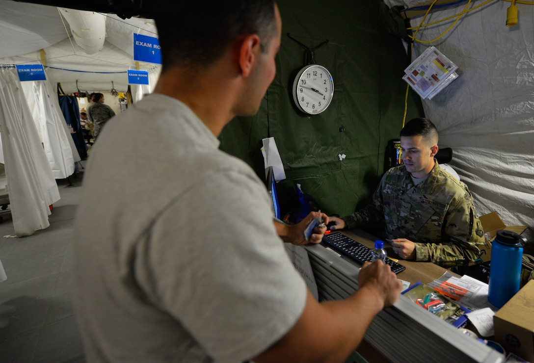 U.S. Air Force Senior Airman Jeffrey Mangione, a medical technician assigned to the 332nd Expeditionary Medical Group, checks in a patient at the reception area of the Expeditionary Medical Support System tent May 10, 2017, in Southwest Asia. The 332nd EMDG medical staff will transfer from the mobile tent unit to a new permanent clinic facility, marking the last EMEDS tent to close in the Air Force Central Command region. (U.S. Air Force photo by Staff Sgt. Alexander W. Riedel)