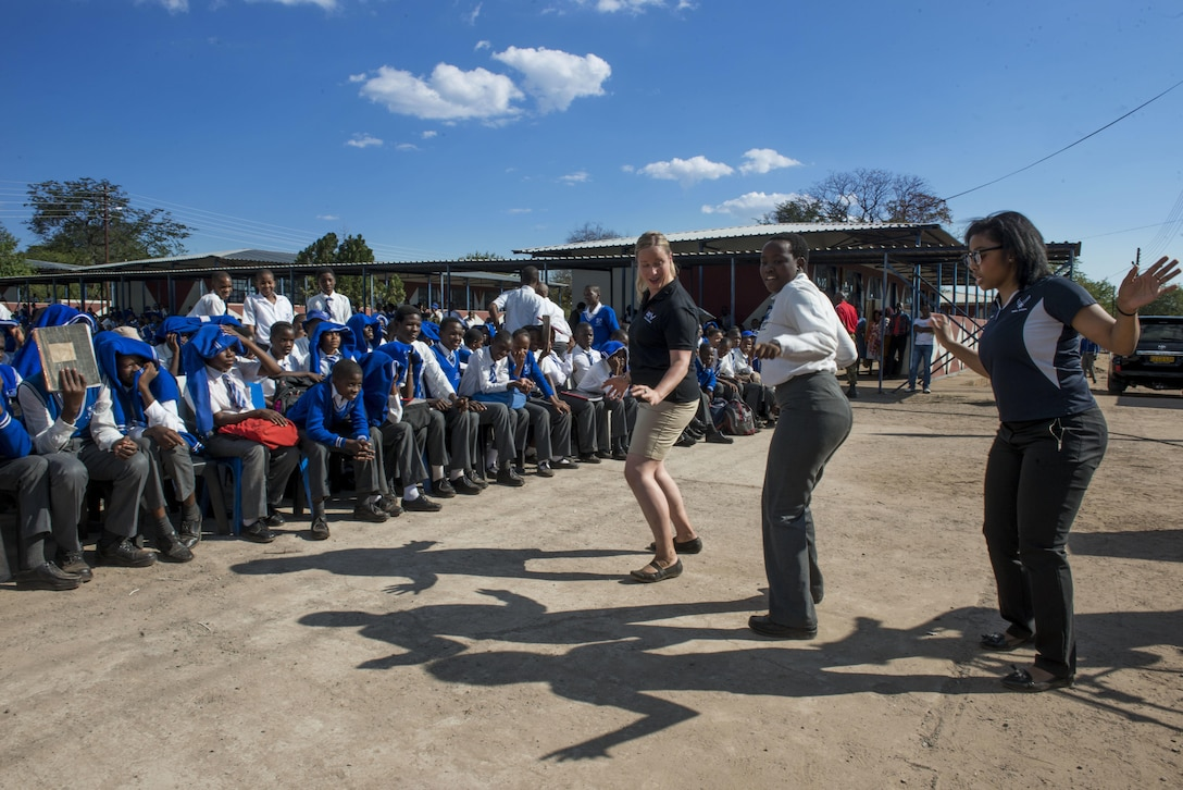 "Staff Sgt. Jill Diem, U.S. Air Forces in Europe Band vocalist, and Capt. Mesha Nelson, USAFE-AFAFRICA public affairs officer, dance with a student from the Chobe Junior Secondary School during a band performance at the school in Kasane, Botswana on May 15, 2017. While supporting the 2017 African Air Chiefs Symposium, the USAFE ""Ambassadors Combo"" performance band partnered with the Botswana Defence Force band to perform several concerts at schools in northern Botswana to inspire the students through the universal language of music. The U.S. And Botswana are co-host of this year's symposium. (U.S. Air Force photo by Staff Sgt. Krystal Ardrey)"