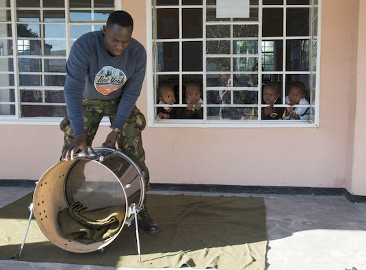 "Lance Cpl. Omphile, Botswana Defence Force Band drummer, sets up his equipment at the Kachikau Primary School while students watch in Kachikau, Botswana on May 17, 2017. While supporting the 2017 African Air Chiefs Symposium, the U.S. Air Forces in Europe ""Ambassadors Combo"" performance band hosted military-to-military band workshops with the BDF Band that focused on improvisation, rehearsal techniques, and synchronization. The bands learned to play two songs together and played for four primary and secondary schools in northern Botswana. (U.S. Air Force photo by Staff Sgt. Krystal Ardrey)"