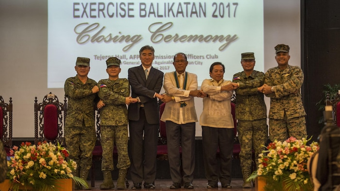 "Armed Forces of the Philippines Maj. Gen. Herminigildo Aquino, left, AFP Gen. Eduardo M. Año, the Honorable Ambassador Sung Y. Kim, Secretary Delfin N. Lorenzana, Under Secretary Ariel Y. Abadilla, AFP Lt. Gen. Oscar T. Lactao, and U.S. Marine Brig. Gen. Brian Cavanaugh stand ""shoulder-to-shoulder"" and shake hands during the Balikatan 2017 closing ceremony at Camp Aguinaldo, Quezon City, May 19, 2017. Aquino is the Philippine assistance exercise director. Año is the Chief of Staff of the AFP. Kim is the U.S. Ambassador to the Philippines. Lorenzana is the Philippine Secretary of National Defense. Abadilla is the Philippine Undersecretary for Civilian Security and Consular Concerns. Lactao is the Philippine exercise director for Balikatan. Cavanaugh is the deputy commander of Marine Corps Forces, Pacific. Balikatan is an annual U.S.-Philippine bilateral military exercise focused on a variety of missions, including humanitarian assistance and disaster relief, counterterrorism, and other combined military operations. ("