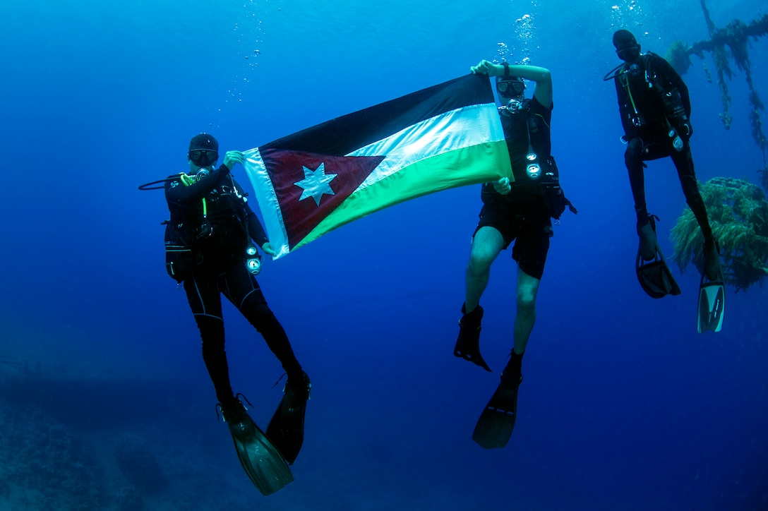 Divers from the Royal Jordanian Navy pose for a photo holding their nation's flag during Exercise Eager Lion 2017. Eager Lion is an annual U.S. Central Command exercise in Jordan designed to strengthen military-to- military relationships between the U.S., Jordan and other international partners. This year's iteration is comprised of about 7,200 military personnel from more than 20 nations that will respond to scenarios involving border security, command and control, cyber defense and battlespace management. (U.S. Navy Combat Camera photo by Mass Communication Specialist 2nd Class Austin L. Simmons)