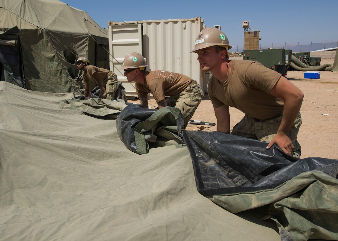 Seabees assigned to Task Group 56.2, Naval Mobile Construction Battalion One, take down a tent in preparation for the end of Exercise Eager Lion 2017. Eager Lion is an annual U.S. Central Command exercise in Jordan designed to strengthen military-to- military relationships between the U.S., Jordan and other international partners. This year's iteration is comprised of about 7,200 military personnel from more than 20 nations that will respond to scenarios involving border security, command and control, cyber defense and battlespace management. (U.S. Navy Combat Camera photo by Mass Communication Specialist 2nd Class Austin L. Simmons)