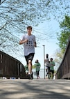 Hayden Santiago, a Hanscom Middle School student, and others run across a bridge during this year's HOPA race at Castle Park on base May 17. The annual three-mile race is named after the Hopa Crabapple tree that was planted near the finish line of the race 32 years ago. (U.S. Air Force photo by Linda LaBonte Britt)