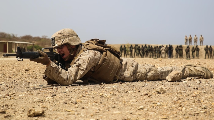 A Marine with Special Purpose Marine Air-Ground Task Force – Crisis Response – Africa, calls out commands during a buddy rushing demonstration for members of Senegal's Compagnie Fusilier de Marin Commando prior to a fire and maneuver range at Thies, Senegal, May 3, 2017.  Marines with SPMAGTF-CR-AF and the COFUMACO conducted a four-week training exercise that included advanced combat firing techniques, a machine gun range and a live-fire platoon attack range.