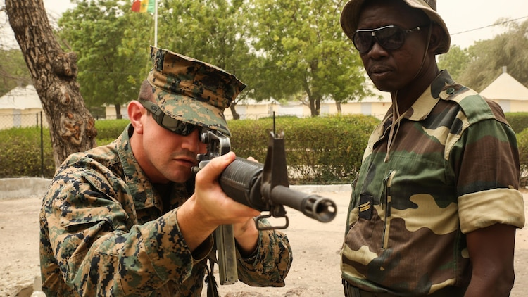 Sgt. Timothy Kuklis, an assaultman with Special Purpose Marine Air-Ground Task Force – Crisis Response – Africa, demonstrates the standing firing position to a member of Senegal's Compagnie Fusilier de Marin Commando during a four-week training exercise at Toubakouta, Senegal, April 12, 2017. Marines with SPMAGTF-CR-AF and the COFUMACO conducted a four-week training exercise that included advanced combat firing techniques, a machine gun range and a live-fire platoon attack range.