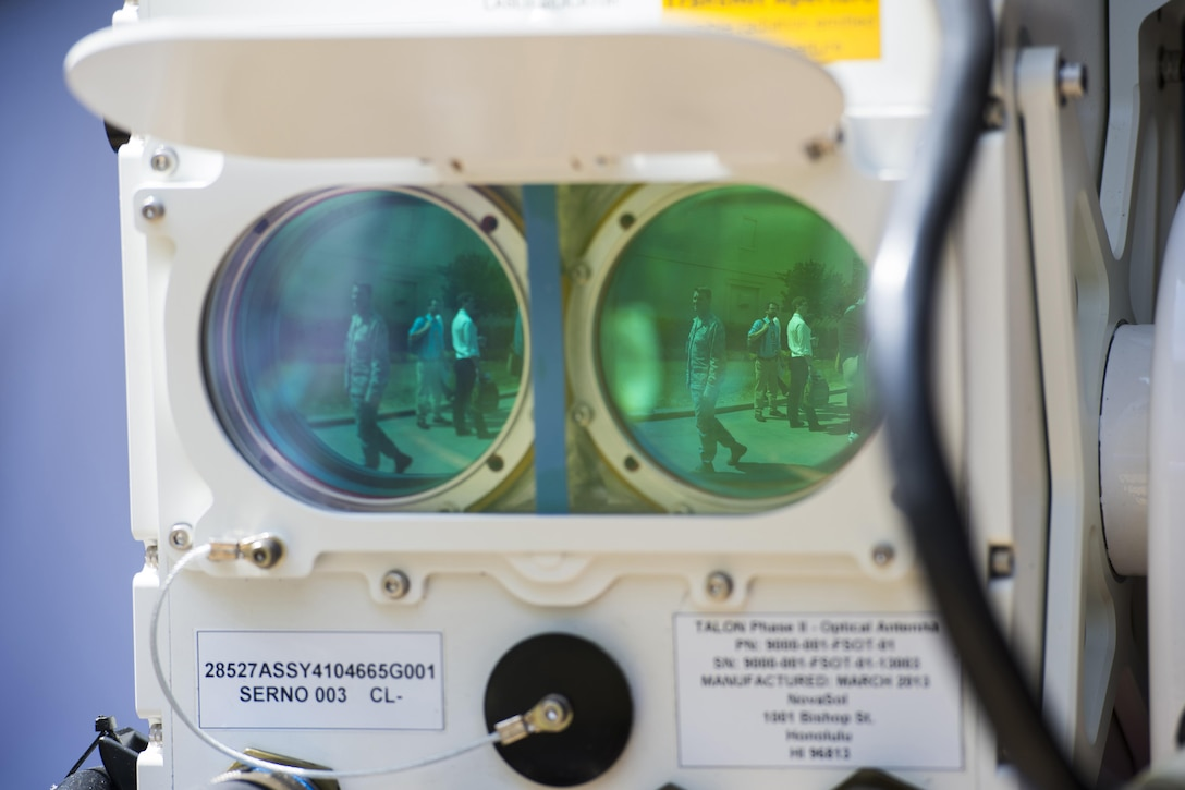 A reflection of people walking appears in lenses from an optical data transmission device.