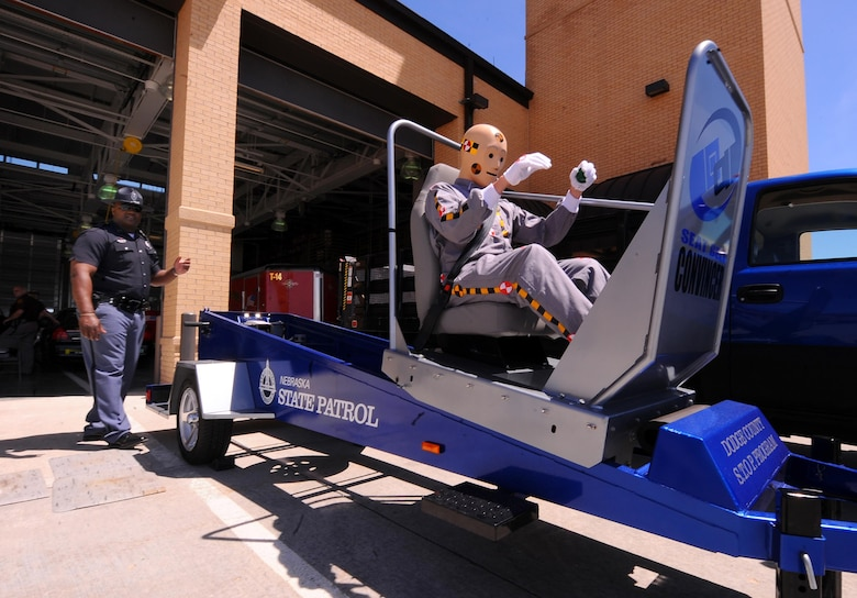 A Nebraska State Trooper uses a training aid to demonstrate the importance of seatbelts and child-restraints, even at relatively slow speeds, as part of a previous 55th Wing Safety Day. In addition to the typical booths manned by safety-conscious organizations like local energy providers, law enforcement agencies and non-profits, this event will include a motorcycle awareness demonstration, face-painting and balloons, military working dog demonstrations and an up-close look at the Omaha police department's helicopter, ABLE 1. Food trucks will also be on-site to provide dining options for attendees.