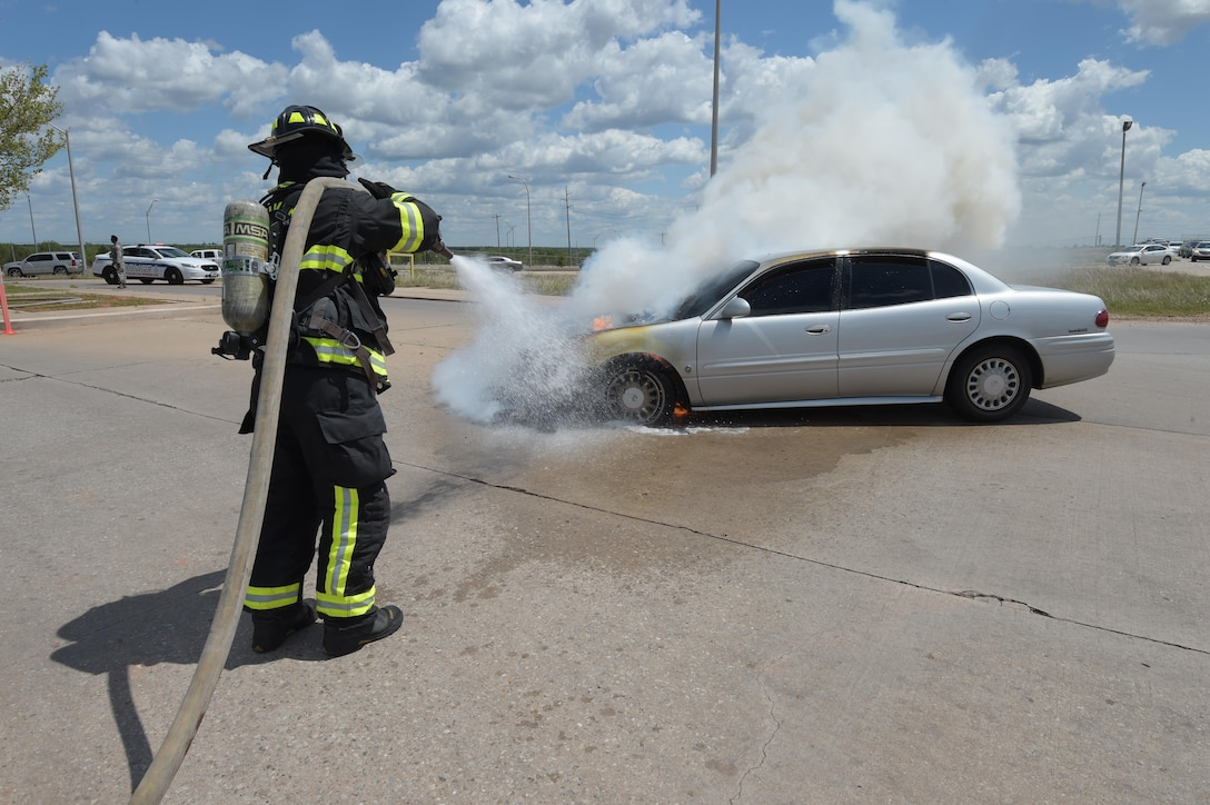 William Green, a Tinker Fire and Emergency Services firefighter, sprays water on a vehicle which caught fire May 4, 2017, at Tinker Air Force Base, Okla. The privately owned vehicle developed mechanical trouble and caught fire near the Oklahoma City Air Logistics Complexs' building 9001. The fire was quickly and safely extinguished using water and powder while traffic was diverted to an alternate route as workers completed their shifts. Tinker Fire and Emergency Services is a division of the 72nd Civil Engineer Squadron. (U.S. Air Force photo/Greg L. Davis)