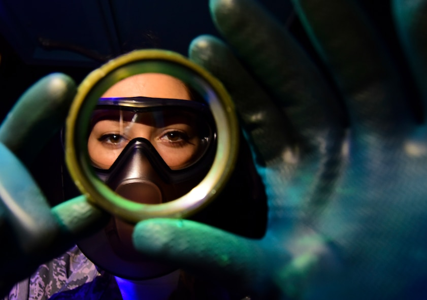 Airman 1st Class Lacy Weeks, a 1st Maintenance Squadron non-destructive inspection technician, inspects an aircraft part under black light at Joint Base Langley-Eustis, Va., May 4, 2017. The technicians use tools including X-ray, magnetic, chemical and black light systems to check for destructive faults in parts and equipment. (U.S. Air Force photo/Staff Sgt. Natasha Stannard)