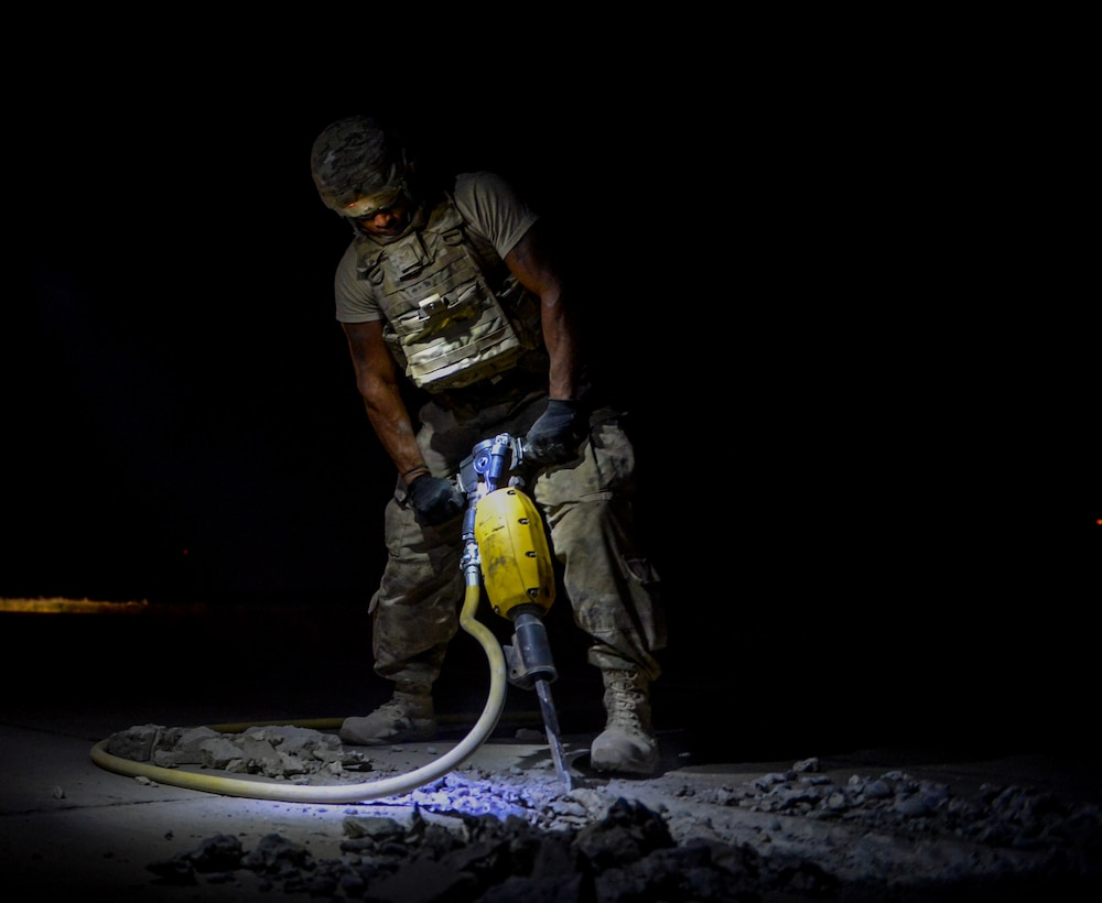 A member of the 1st Expeditionary Civil Engineer Group jackhammers a damaged section of the flightline at Qayyarah West Airfield, Iraq, during a restoration project May 16, 2017. Qayyarah West is an airfield in northern Iraq's Ninawa Province and serves as the logistical hub and strategic launching pad resupplying the frontlines in an attempt to recapture Mosul. (U.S. Air Force photo/Staff Sgt. Michael Battles)