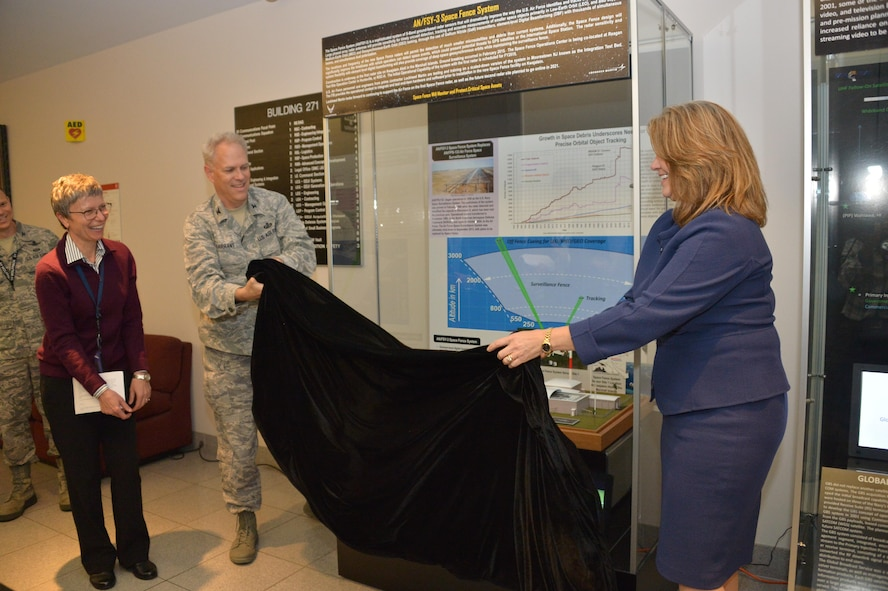 Michele Evans, vice president and general manager of Integrated Warfare Systems and Sensors for Lockheed Martin Rotary and Mission Systems, accompanied by Robert Condren, Don Tomajen and Nancy FitzGerald, assist Col. Phil Garrant, director of the Space and Missile Systems Center's Space Superiority Directorate in unveiling a new information display at the SMC Heritage Center at Los Angeles Air Force Base in El Segundo, California, May 11, 2017.
